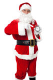 Santa pointing at an antique time piece Royalty Free Stock Images