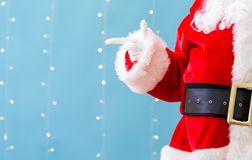 Santa with pointing gesture. On a shiny light blue background stock photography