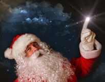 Santa pointing with magical light to the sky royalty free stock photos