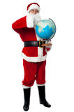 Santa pointing out a continent on globe Royalty Free Stock Photography
