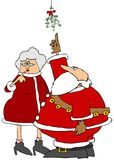 Santa pointing to the mistletoe that he and Mrs. Claus are under Stock Photos