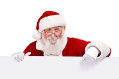 Santa pointing in white sign. Santa Claus pointing in white blank sign with smile, isolated on white background Royalty Free Stock Image