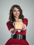 Santa pomagiera dziewczyna uśmiecha się Bożenarodzeniowego prezent w małym złotym pudełku i daje kamera Fotografia Royalty Free