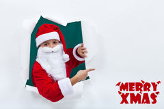 Santa popping out from hole and pointing to copy space Royalty Free Stock Photography