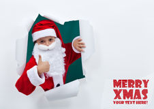 Santa popping out of torn edges hole with thumbs up sign Royalty Free Stock Photography