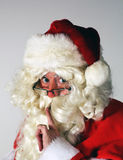 Santa portrait. Santa Clause portrait with Santa looking over glasses and gesturing quiet Royalty Free Stock Image