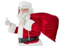 Santa positiva com seus saco e polegares acima Foto de Stock Royalty Free
