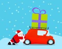 Santa poussant la voiture de Noël avec le cadeau Photo stock