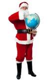 Santa précisant un continent sur le globe Photographie stock libre de droits