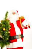 Santa with present and christmas tree Stock Images