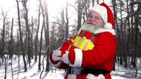 Santa with presents outdoor. Happy Santa Claus, forest background stock footage