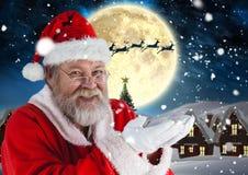 Santa pretending to hold digital generated snow. Portrait of santa pretending to hold digital generated christmas gifts at night royalty free stock photo