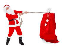 Santa pulling gifts sack. Over white background Stock Images