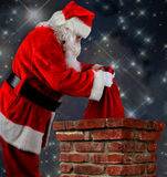 Santa Putting Bag into Chimneys Royalty Free Stock Image