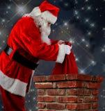 Santa Putting Bag em chaminés Imagem de Stock Royalty Free