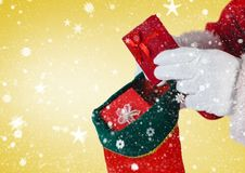 Santa putting gifts in christmas stocking Royalty Free Stock Photography