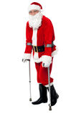 Santa que anda com a ajuda das muletas Imagem de Stock Royalty Free