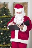 Santa que cheking sua lista Imagem de Stock