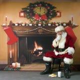 Santa que come las galletas y la leche Fotografía de archivo libre de regalías