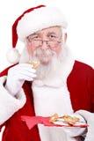 Santa que come o bolinho Fotografia de Stock