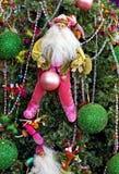 Santa que cuelga en un árbol de navidad adornado colorido Fotos de archivo libres de regalías