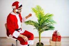 Santa que decora uma árvore Imagens de Stock