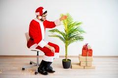 Santa que decora uma árvore Fotos de Stock Royalty Free