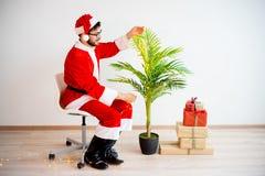 Santa que decora uma árvore Imagem de Stock