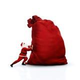 Santa que empurra o saco enorme Isolado no branco Fotografia de Stock