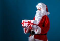 Santa que guarda caixas de presente do Natal foto de stock