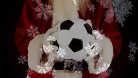Santa que guarda um futebol nos flocos de neve video estoque