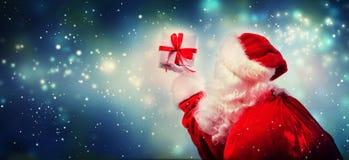 Santa que guarda um presente do Natal foto de stock