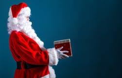 Santa que guarda um presente do Natal imagem de stock