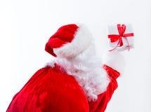 Santa que guarda um presente do Natal fotos de stock