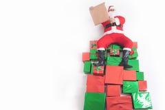 Santa que senta-se em caixas de presente grandes e que lê a lista de objetivos pretendidos Imagens de Stock
