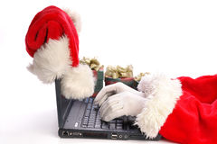 Santa que usa la computadora portátil Foto de archivo libre de regalías