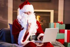 Santa que usa o computador Foto de Stock Royalty Free