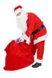 Santa reaches for a gift Royalty Free Stock Photography