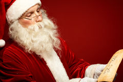 Santa reading letter. Portrait of serious Santa Claus reading Christmas letter in isolation Stock Images