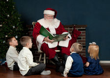 Santa reading to kids Stock Photo