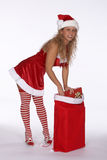 Santa in Red Dress with Stripped Stockings Bending Over Gift Bag Royalty Free Stock Photography