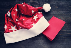 Santa red hat and a red empty card for an inscription on wooden background Royalty Free Stock Photography