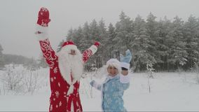 Santa and granddaughter Snow Maiden in the snow-covered forest during the day dancing. Santa in a red hat and with a white beard and a beautiful merry stock footage