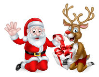 Santa and Reindeer with Christmas Gift. Santa Claus and his Reindeer wrapping or unwrapping a Christmas gift Royalty Free Stock Photos