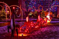 Santa and reindeer pulling sleigh. A Santa in sleigh with reindeer are part of a village square Christmas display. Focus on Santa royalty free stock image