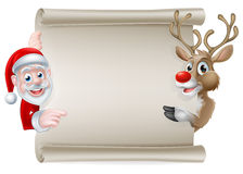 Santa Reindeer Scroll. Cartoon Christmas scroll sign of Santa Claus and his reindeer pointing at a scroll banner Royalty Free Stock Image