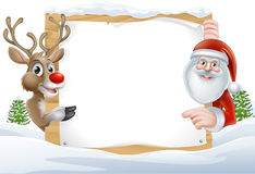 Santa and Reindeer Sign. Cartoon Reindeer and Santa pointing at a snow covered sign in a winter landscape Royalty Free Stock Photo