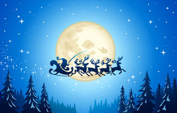 Santa and reindeer in sky. Santa Claus and reindeer flying midair in front of moon in blue sky over forest Royalty Free Stock Photography