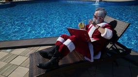 Santa relaksuje przy basenem i robi szalonemu dowcipowi z laptopem zdjęcie wideo