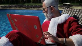 Santa relax at pool and do crazy joke with laptop